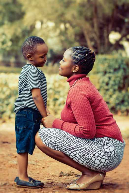 Mother stooping down as son wishing her Happy Mother's Day